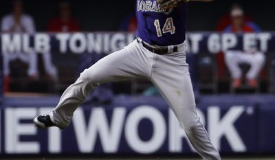 Colorado Rockies second baseman Josh Rutledge leaps to make a throw to first base on a single by Philadelphia Phillies' Chase Utley during the fourth inning of a baseball game, Monday, May 26, 2014, in Philadelphia. (AP Photo/Matt Slocum)