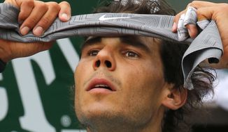 Spain's Rafael Nadal adjusts his head band during a break in the first round match of the French Open tennis tournament against Robby Ginepri of the U.S. at the Roland Garros stadium, in Paris, France, Monday, May 26, 2014. (AP Photo/Michel Spingler)