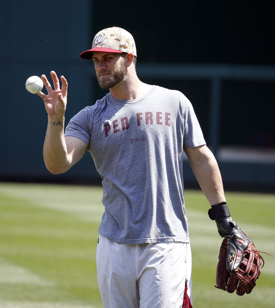 Washington Nationals left fielder Bryce Harper catches a ball without using his injured left hand before a baseball game at Nationals Park Monday, May 26, 2014, in Washington. Harper has been on the disabled list with an injured left hand. (AP Photo/Alex Brandon)