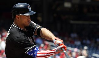 Miami Marlins' Giancarlo Stanton hits a double while wearing a red, white, and blue arm sleeve, during the first inning of a baseball game at Nationals Park on Memorial Day, Monday, May 26, 2014, in Washington. (AP Photo/Alex Brandon)