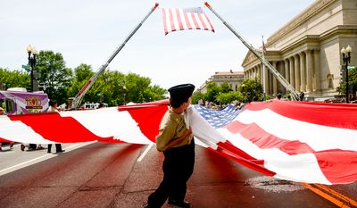 Cadet Christian Stern with the ROTC at Paint Branch High School in Burtonsville, Md. helps keep a large American flag off the ground as he and other cadets carry it down down Constitution Avenue during the National Memorial Day Parade, Washington, D.C., Monday, May 26, 2014. (Andrew Harnik/The Washington Times)