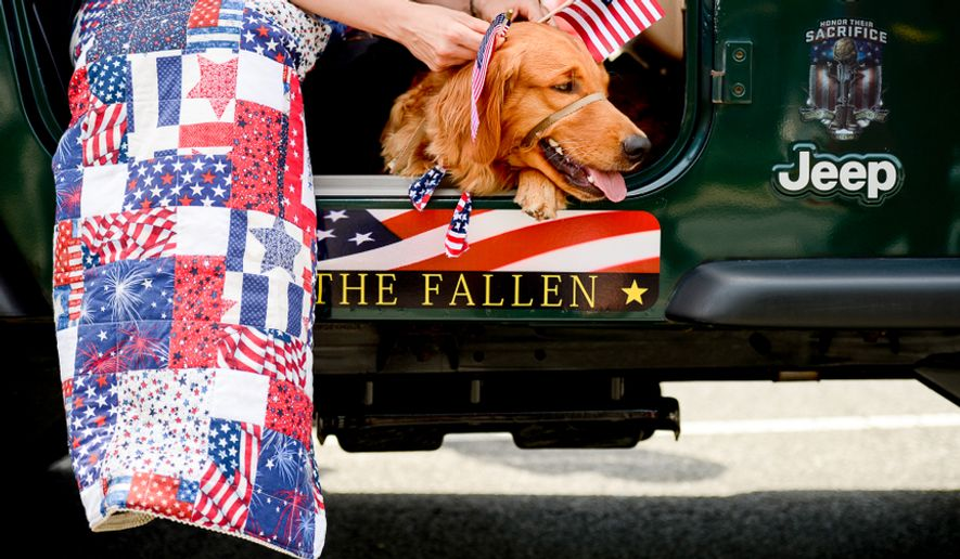 Retired Army Military Intelligence Officer Angelee Andoe of Lorton, Va., sits with her service dog, Franklin Delano Roosevelt, a golden retriever as they get ready to march with a group of Hero Dogs in the National Memorial Day Parade along Constitution Avenue, Washington, D.C., Monday, May 26, 2014. Andoe, who suffers from PTSD, is helped by F.D.R. who is given to her by Hero Dogs, a nonprofit which helps provide improved quality of life to veterans with disabilities. (Andrew Harnik/The Washington Times)