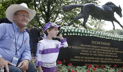 FILE - In this June 9, 2012 file photo, retired jockey Ron Turcotte, left, who rode Secretariat to the Triple Crown in 1973, poses for photos with Kenny Foudy, 5, next to a statue of the race horse prior to the Belmont Stakes at Belmont Park in Elmont, N.Y.  Kentucky Derby and Preakness Stakes winner California Chrome is preparing for the final leg of the Triple Crown, the Belmont Stakes, on June 7, 2014.  (AP Photo/Mark Lennihan, File)