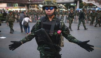 "A Thai soldier gestures as he and his colleagues guard the Victory Monument during an anti-coup demonstration in Bangkok, Thailand Monday, May 26, 2014. Bolstered by a royal endorsement Monday to run the country after last week's coup, Thailand's junta leader warned citizens not to cause trouble, not to criticize, not to protest, or else face a return to the ""old days"" of street violence. (AP Photo/Wason Wanichakorn)"