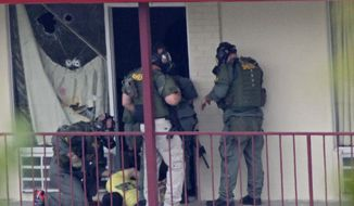 Knoxville police SWAT team officers examine a suspect outside a room at the Days Inn hotel Tuesday, May 27, 2014, in Knoxville, Tenn. (AP Photo/Wade Payne) ** FILE **