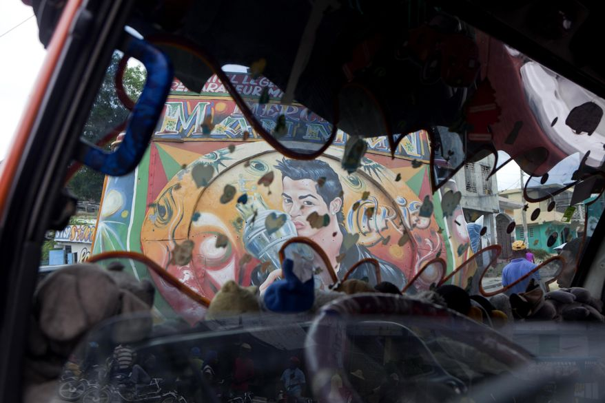 In this May 21, 2014 photo, a mural of Portugal's soccer player Cristiano Ronaldo decorates the back of a tap-tap passenger bus, seen through the windshield of another bus, in Port-au-Prince, Haiti. Several artists have spent hours in a Port-au-Prince bus garage, decorating the vehicles with the faces of their favorite soccer players ahead of the World Cup in Brazil. (AP Photo/Dieu Nalio Chery)