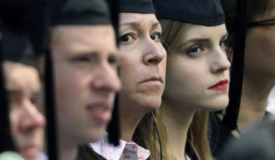 In this Sunday, May 25, 2014 photo, actress Emma Watson, right, sits beside a woman, left, later seen wearing a badge and with a handgun visible at her side, during commencement services at Brown University in Providence, R.I.  A Brown spokesman said Tuesday, May 27, 2014, he was unable to answer questions about why the British actress had the undercover armed guard sitting with her during graduation ceremonies. (AP Photo/Steven Senne)