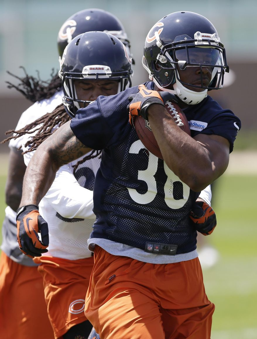 Chicago Bears running back Shaun Draughn (38) runs with a ball past safety Danny McCray during NFL football practice in Lake Forest, Ill., Tuesday, May 27, 2014. (AP Photo/Nam Y. Huh)