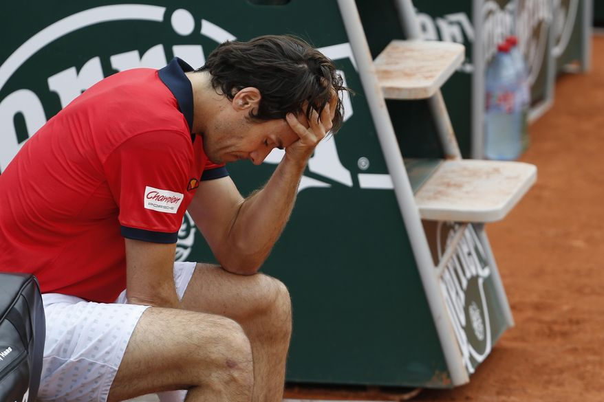 Germany's Tommy Haas holds his head as a right shoulder injury forces him to retire from the first round match of the French Open tennis tournament against Estonia's Jurgen Zopp at the Roland Garros stadium, in Paris, France, Tuesday, May 27, 2014. (AP Photo/Darko Vojinovic)