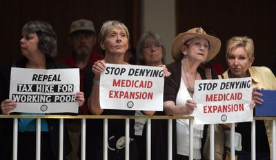 People hold signs during a Moral Tuesday demonstration at the North Carolina General Assembly, Tuesday, May 27, 2014, in Raleigh, N.C. (AP Photo/The News & Observer, Corey Lowenstein)