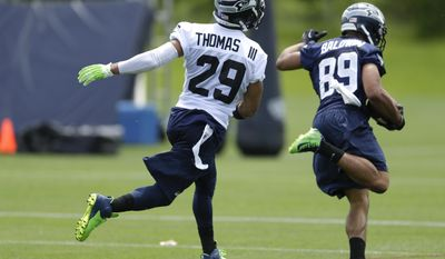 Seattle Seahawks' free safety Earl Thomas (29) runs after Doug Baldwin (89) after Baldwin made a reception in a drill during an NFL football organized team activity, Tuesday, May 27, 2014, in Renton, Wash. (AP Photo/Ted S. Warren)