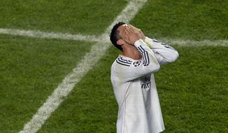 Real's Cristiano Ronaldo covers his face after winning the Champions League final soccer match between Atletico Madrid and Real Madrid in Lisbon, Portugal, Saturday, May 24, 2014. (AP Photo/Paulo Duarte)