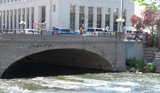 Pedestrians and traffic cross the Truckee River in Reno, Nev., Tuesday, May 27, 2014, on the historic Virginia Street bridge. Built in 1905, demolition and reconstruction of the bridge has been postponed perhaps into next year due to a delay in federal permitting for a comprehensive flood control project. The bridge became legendary after it was portrayed by Hollywood and the news media as the site where people tossed wedding rings into the Truckee after securing divorces at the nearby courthouse.  (AP Photo/By Scott Sonner).