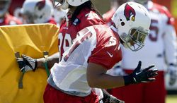 In this May 20, 2014, photo, Arizona Cardinals' Kevin Minter (51) works on blocking and rushing drills with teammate Andre Ellington during an NFL football organized team activity in Tempe, Ariz. (AP Photo/Ross D. Franklin)