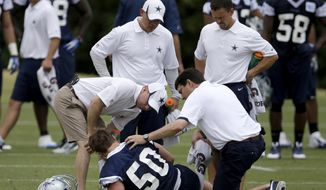 Dallas Cowboys' Sean Lee (50) is attended to by the athletic training staff after Lee suffered a injury during an NFL football organized team activity, Tuesday, May 27, 2014, in Irving, Texas. (AP Photo/Tony Gutierrez)