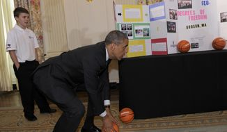 President Barack Obama tries to catch a basketball as Gerry McManus, 13, of Hudson, Mass., watches, during a tour of the 2014 White House Science Fair exhibits that are on display in the State Dining Room at the White House in Washington, Tuesday, May 27, 2014. McManus and two other students showed Obama their basketball catapult. Obama was celebrating the student winners of a broad range of science, technology, engineering and math (STEM) competitions from across the country. (AP Photo/Susan Walsh)