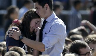 A couple embrace before a memorial service for the victims and families of Friday's rampage at Harder Stadium on the campus of University of California, Santa Barbara on Tuesday, May 27, 2014 in the Isla Vista area near Goleta, Calif. Sheriff's officials said Elliot Rodger, 22, went on a rampage near the University of California, Santa Barbara, stabbing three people to death at his apartment before shooting and killing three more in a crime spree through a nearby neighborhood. (AP Photo/Chris Carlson)
