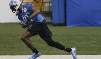 Detroit Lions receiver Calvin Johnson runs through an NFL football organized team activity in Allen Park, Mich., Wednesday, May 28, 2014. (AP Photo/Carlos Osorio)