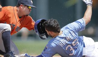 Kansas City Royals' Eric Hosmer (35) beats the tag by Houston Astros second baseman Jose Altuve, left, during the fourth inning of a baseball game at Kauffman Stadium in Kansas City, Mo., Wednesday, May 28, 2014. Hosmer was safe with a double on the play. (AP Photo/Orlin Wagner)