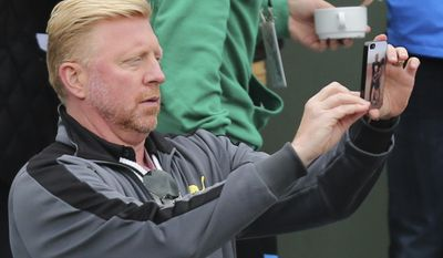 Former tennis ace Boris Becker takes an image with his mobile phone during the second round match of the French Open tennis tournament between Serbia's Novak Djokovic and France's Jeremy Chardy  at the Roland Garros stadium, in Paris, France, Wednesday, May 28, 2014. (AP Photo/David Vincent)