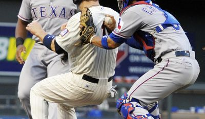 Minnesota Twins' Josh Willingham, center, is tagged out in a rundown between third and home by Texas Rangers catcher Robinson Chirinos, right, as third baseman Adrian Beltre stands near in the second inning of a baseball game Wednesday, May 28, 2014, in Minneapolis. (AP Photo/Jim Mone)