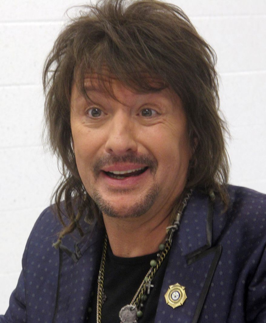 "Bon Jovi guitarist Richie Sambora speaks to reporters in Toms River, N.J., before a performance at an anti-drug forum on May 27, 2014. Sambora unveiled a new song, ""Lighthouse"" that will raise money for a drug treatment center in New Jersey.(AP Photo/Wayne Parry)"
