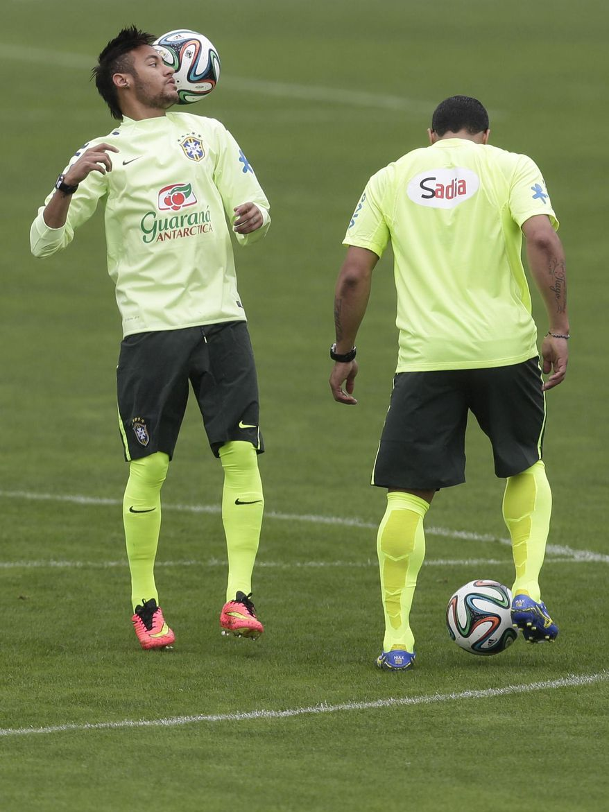 Brazil's Neymar, left, controls the ball during a practice session at the Granja Comary training center in Teresopolis, Brazil, Wednesday, May 28, 2014. Brazil will host the World Cup soccer tournament that starts in June. (AP Photo/Hassan Ammar)