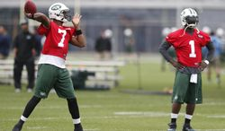 New York Jets quarterback Geno Smith, left, throws a pass while quarterback Michael Vick looks on during an NFL football organized team activity, Wednesday, May 28, 2014, in Florham Park, N.J. (AP Photo/Julio Cortez)