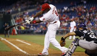 Philadelphia Phillies' Ryan Howard follows through after hitting an RBI single off Colorado Rockies starting pitcher Jordan Lyles during the third inning of a baseball game, Wednesday, May 28, 2014, in Philadelphia. At right is catcher Wilin Rosario. (AP Photo/Matt Slocum)