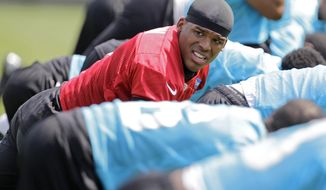 Carolina Panthers' quarterback Cam Newton stretches with teammates during an NFL football organized team activity in Charlotte, N.C., Wednesday, May 28, 2014. (AP Photo/Bob Leverone)