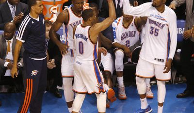 Oklahoma City Thunder guard Russell Westbrook (0) is greeted by teammates, guard Thabo Sefolosha (25), forward Serge Ibaka (9), and forward Kevin Durant (35) after being pulled in the last moments of Game 4 of the Western Conference finals NBA basketball playoff series in Oklahoma City, Tuesday, May 27, 2014. (AP Photo/Garett Fisbeck)