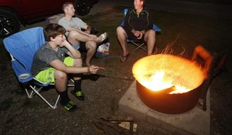 In this photo taken on May 21, 2014, Cole Betsinger, 14, left, his father Randy Betsinger, center, and Lee Dallenbach all of Charles City circle around a campfire at George Wyth State Park in Waterloo, Iowa. State Park officials are asking Iowa campers to burn all their firewood to slow the spread of the emerald ash borer. The insect has been found in nine Iowa counties: Allamakee, Des Moines, Jefferson, Cedar, Union, Black Hawk, Wapello, Bremer and Jasper. (AP Photo/Waterloo Courier, Matthew Putney)