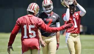 San Francisco 49ers quarterback Colin Kaepernick, center, jokes with teammate Michael Crabtree (15) during an NFL football organized team activity, Wednesday, May 28, 2014, in Santa Clara, Calif. (AP Photo/Marcio Jose Sanchez)