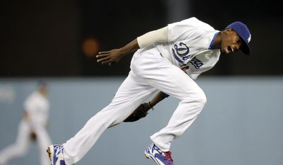 Los Angeles Dodgers second baseman Dee Gordon can't catch a single hit by Cincinnati Reds' Jay Bruce during the seventh inning of a baseball game on Tuesday, May 27, 2014, in Los Angeles. (AP Photo/Jae C. Hong)