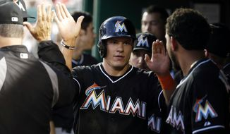 Miami Marlins' Derek Dietrich, center, celebrates scoring with his teammates during the fourth inning of a baseball game against the Washington Nationals at Nationals Park, Wednesday, May 28, 2014, in Washington. (AP Photo/Alex Brandon)