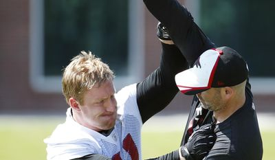 Atlanta Falcons defensive end Kroy Biermann (71) works with linebackers coach Mark Collins during a NFL football practice, Wednesday, May 28, 2014, in Flowery Branch, Ga. (AP Photo/John Bazemore)