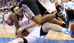 San Antonio Spurs forward Boris Diaw, top, dives over Oklahoma City Thunder forward Nick Collison to try and take the ball in the fourth quarter of Game 4 of the Western Conference finals NBA basketball playoff series in Oklahoma City, Tuesday, May 27, 2014.  (AP Photo/Sue Ogrocki)