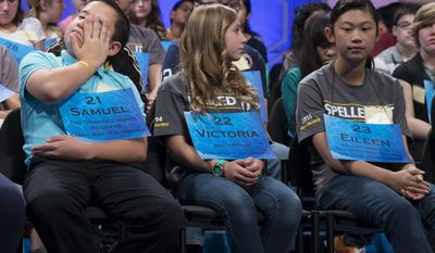 From left, Samuel Littrell of Placentia, Calif., Victoria Phillips of Yermo, Calif., and Eileen Xue of Tulare, Calif., wait for their turn to spell during the preliminary round of the National Spelling Bee, Wednesday, May 28, 2014, in Oxon Hill, Md. (AP Photo/ Evan Vucci)