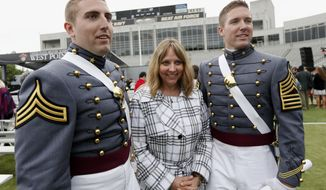U.S. Military Academy graduates Michael Lesmeister, left, and his brother Jeffrey Daniel Lesmeister, of Anoka, Minn. stand with their mother Lynn Sheree Lesmeister after a graduation and commissioning ceremony, Wednesday, May 28, 2014, in West Point, N.Y. (AP Photo/Mike Groll)