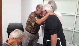 Office of Hawaiian Affairs CEO Kamanaopono Crabbe, second left, greets a supporter at an agency meeting in Honolulu on Thursday, May 29, 2014. Crabbe says the agency should take more time than originally planned in its nation-building process. (AP Photo/Cathy Bussewitz)