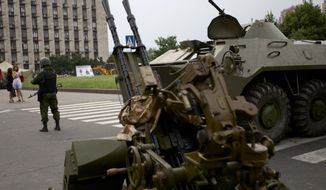 A Pro-Russian militia member guards next to an APC and anti-aircraft gun, outside the administrational building in Donetsk, Ukraine, on Thursday, May 29, 2014. Pro-Russian militia in eastern Ukraine shot down a government military helicopter Thursday amid heavy fighting around Slovyansk, killing 14 soldiers including a general. (AP Photo/Ivan Sekretarev)