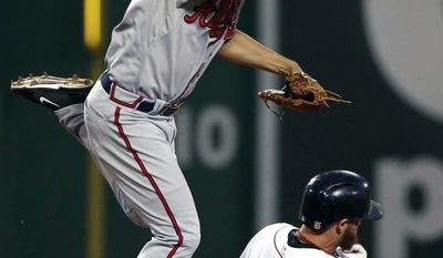 Atlanta Braves shortstop Andrelton Simmons looks down to first after turning a double play over Boston Red Sox's Jonny Gomes (5) during the fourth inning of a baseball game at Fenway Park in Boston, Thursday, May 29, 2014. (AP Photo/Winslow Townson)