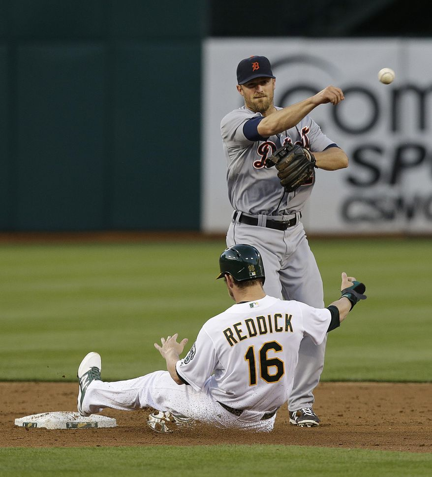 Detroit Tigers shortstop Danny Worth, top, throws to first base to turn a double play on Oakland Athletics' Eric Sogard, after forcing out Josh Reddick (16) at second base during the third inning of a baseball game in Oakland, Calif., Wednesday, May 28, 2014. (AP Photo/Jeff Chiu)