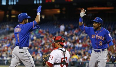 New York Mets' Chris Young, left, and Curtis Granderson, right, celebrate near Philadelphia Phillies catcher Carlos Ruiz after Young's two-run home run during the fourth inning of a baseball game, Thursday, May 29, 2014, in Philadelphia. (AP Photo/Matt Slocum)