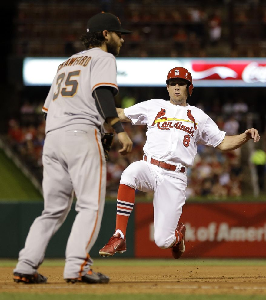 St. Louis Cardinals' Peter Bourjos, right, slides safely into third on a sacrifice bunt by Jaime Garcia as San Francisco Giants shortstop Brandon Crawford covers third during the fifth inning of a baseball game, Thursday, May 29, 2014, in St. Louis. (AP Photo/Jeff Roberson)