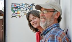 In this May 20, 2014 photo, Susan and Larry Dach, 2014 summer campground hosts at Dragoon Campground north of Spokane, Wash., stand by their RV in Spokane. The Dachs have traveled and camped in their RV throughout the western and northern United States, and as far north as Alaska, since retiring in 2008. The couple, who cut costs by earning free camping as hosts, say they're planning their future trips to cover the South. (AP Photo/The Spokesman-Review, Rich Landers)  COEUR D'ALENE PRESS OUT
