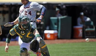 Detroit Tigers' Miguel Cabrera, rear, scores past Oakland Athletics catcher Derek Norris on a double by Victor Martinez during the seventh inning of a baseball game Thursday, May 29, 2014, in Oakland, Calif. (AP Photo/Marcio Jose Sanchez)