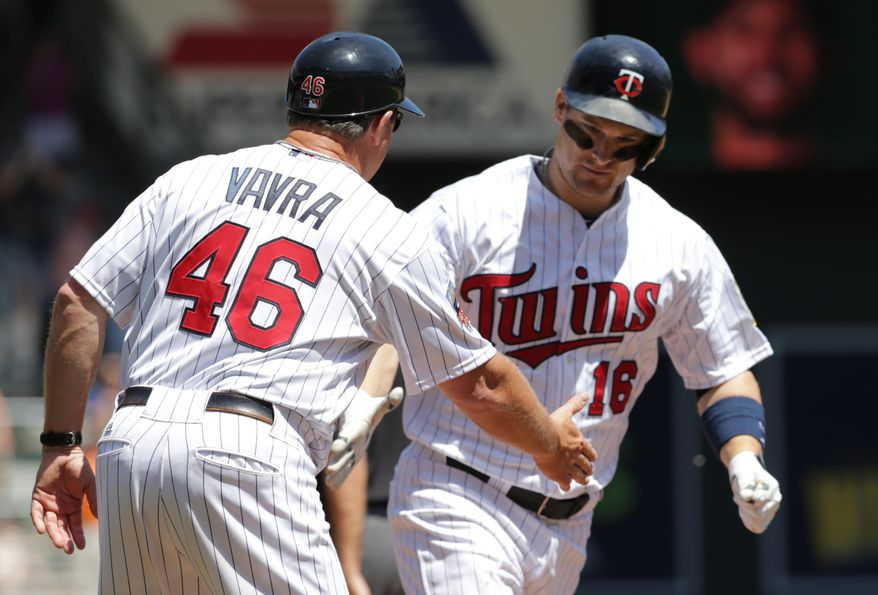 Minnesota Twins' Josh Willingham, right, is congratulated by third base coach Joe Vavra after his go-ahead, two-run home run off Texas Rangers pitcher Nick Martinez in the fifth inning of a baseball game Thursday, May 29, 2014, in Minneapolis. (AP Photo/Jim Mone)