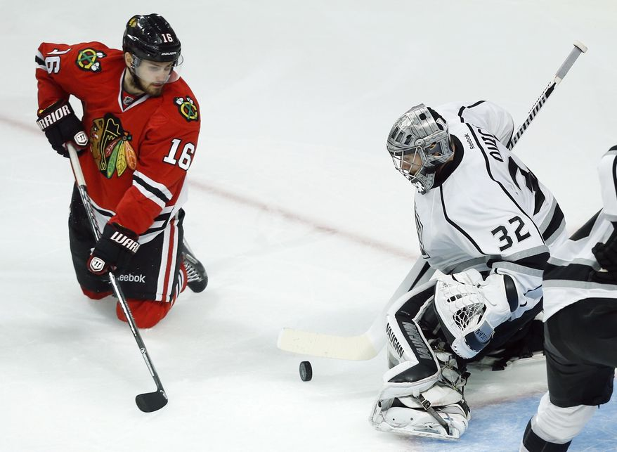 Los Angeles Kings goalie Jonathan Quick (32) blocks a shot by Chicago Blackhawks center Marcus Kruger (16) during the overtime period in Game 5 of the Western Conference finals in the NHL hockey Stanley Cup playoffs Wednesday, May 28, 2014, in Chicago. (AP Photo/Andrew A. Nelles)