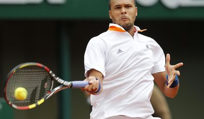France's Jo-Wilfried Tsonga returns the ball to Austria's Jurgen Melzer during the second round match of  the French Open tennis tournament at the Roland Garros stadium, in Paris, France, Wednesday, May 28, 2014. (AP Photo/David Vincent)